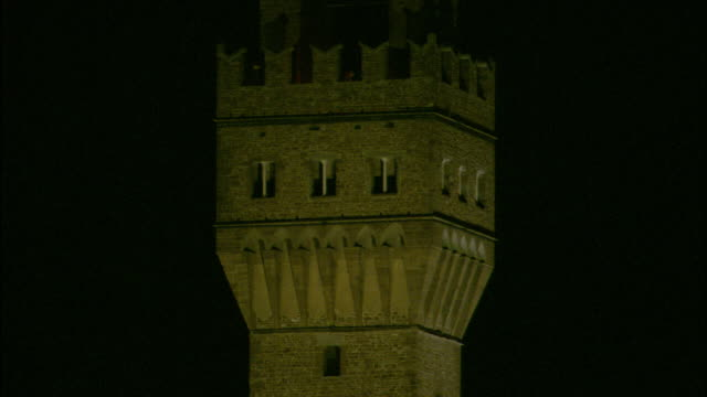 Lights illuminate a crenellated tower in Florence, Italy.