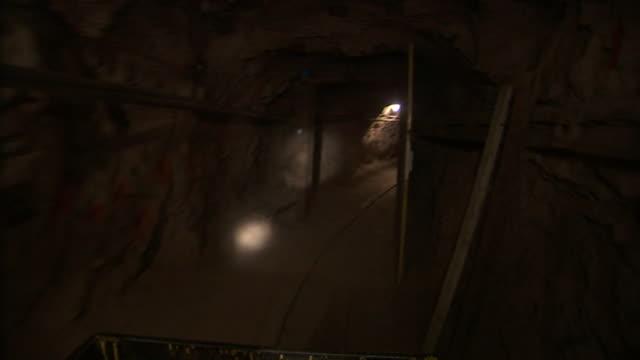 lights illuminate a mine shaft. - mine shaft stock videos and b-roll footage