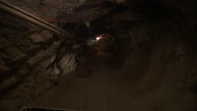 lights illuminate a mine shaft. - mine stock videos & royalty-free footage