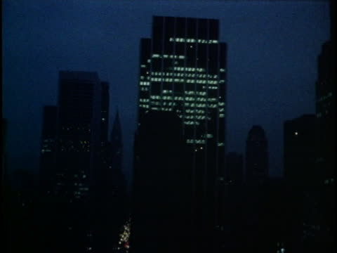 lights illuminate a skyscraper silhouetted against a clear new york city sky. - illuminated stock videos & royalty-free footage