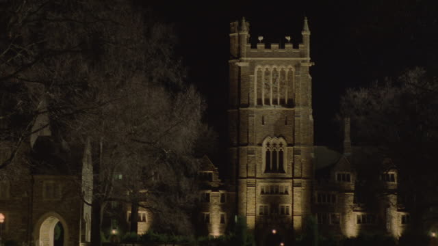 lights illuminate a stone bell tower on a college campus. - school bell stock videos and b-roll footage
