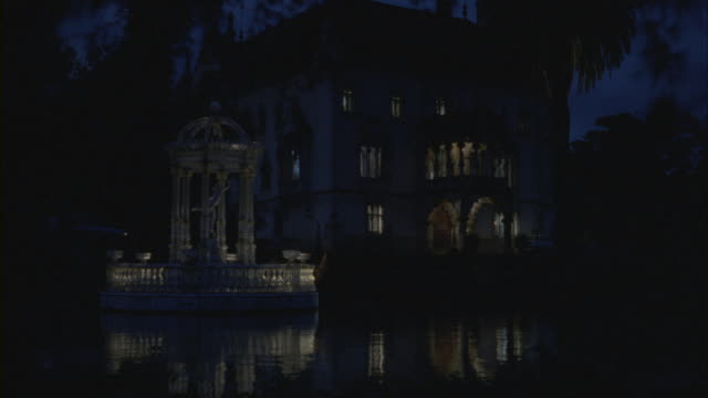 lights illuminate a three story mansion and pond. - standing water stock videos & royalty-free footage