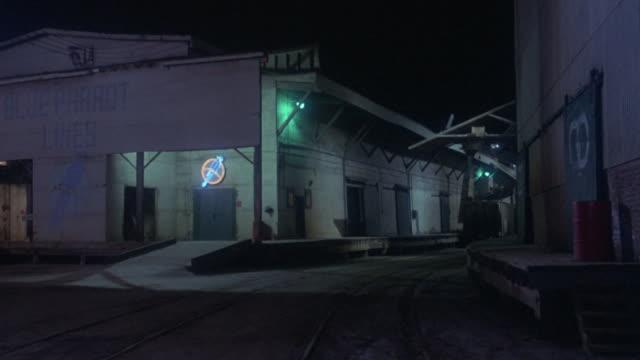 vídeos de stock e filmes b-roll de lights illuminate a warehouse at night. - ausência