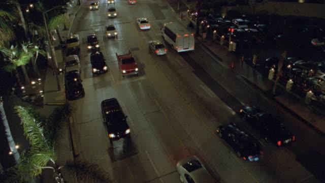 lights illuminate buildings as traffic moves along sunset boulevard in los angeles. - sunset boulevard stock-videos und b-roll-filmmaterial