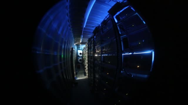 Lights illuminate ethernet cables on mining rigs operating inside a shipping container converted into a mobile cryptocurrency mining farm operated by...