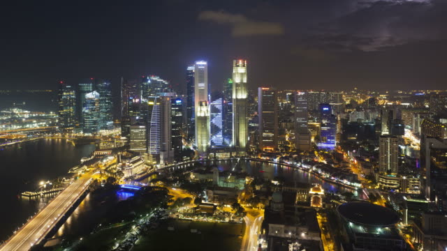 Lights illuminate highrises in the skyline of the financial district of Singapore.