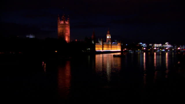 lights illuminate london's westminster abbey, the houses of parliament, and big ben at night. - westminster abbey stock videos & royalty-free footage