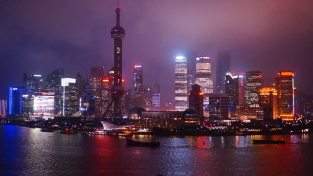 Lights illuminate Pudong area skyscrapers and reflect on the Huang-Po River.