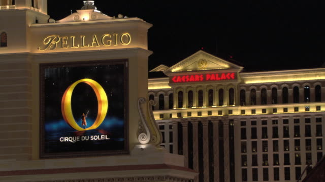 lights illuminate signs for the bellagio las vegas and caesars palace. - bellagio hotel stock videos & royalty-free footage