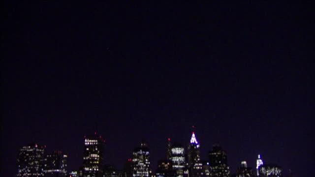 lights illuminate skyscrapers in manhattan at night. - manhattan video stock e b–roll