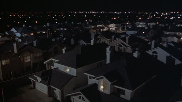 Lights illuminate suburban homes at night.