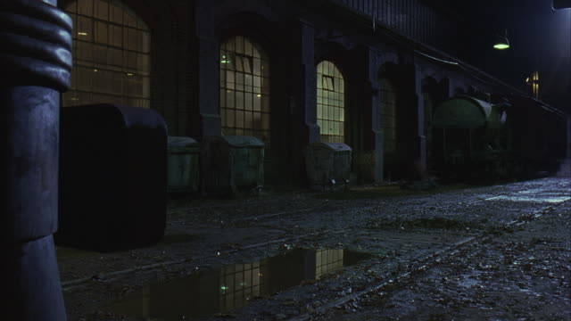 Lights illuminate the arched windows of an abandoned building next to puddles in the mud.
