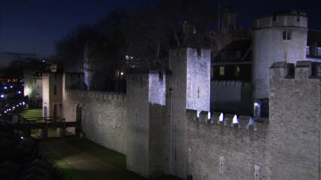 Lights illuminate the castle walls of the Tower of London at night.