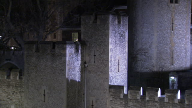 lights illuminate the castle walls of the tower of london at night. - tower of london stock videos & royalty-free footage