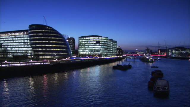 Lights illuminate the City Hall building on the Southbank of the River Thames at night.