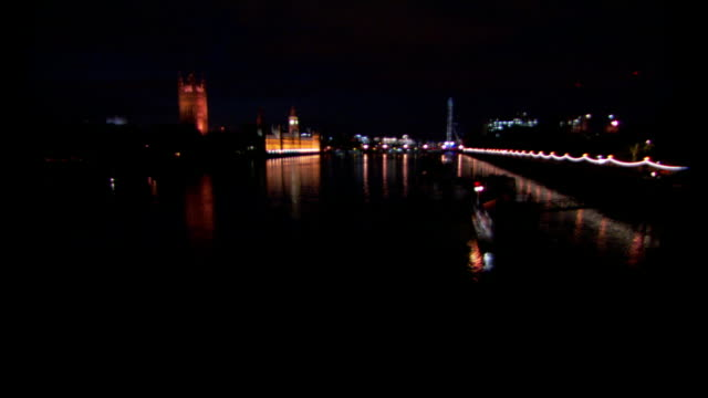 lights illuminate the houses of parliament, westminster abbey and the banks of the river thames at night. - westminster abbey stock videos & royalty-free footage