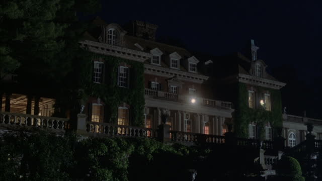 Lights illuminate the lower floor and yard of a huge mansion.