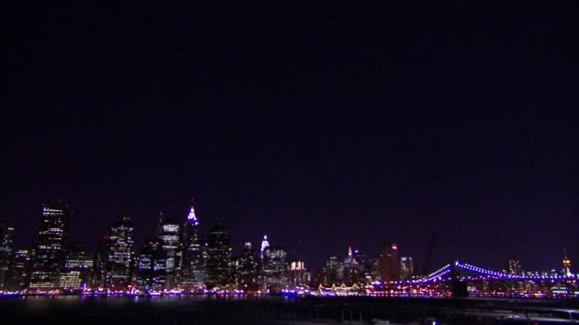 lights illuminate the manhattan skyline at night. - manhattan video stock e b–roll