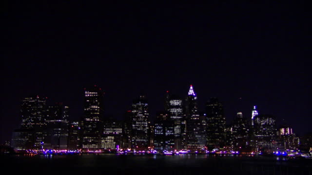 lights illuminate the manhattan waterfront at night. - manhattan video stock e b–roll