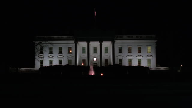 lights illuminate the north side of the white house in washington, dc, at night. - la casa bianca washington dc video stock e b–roll