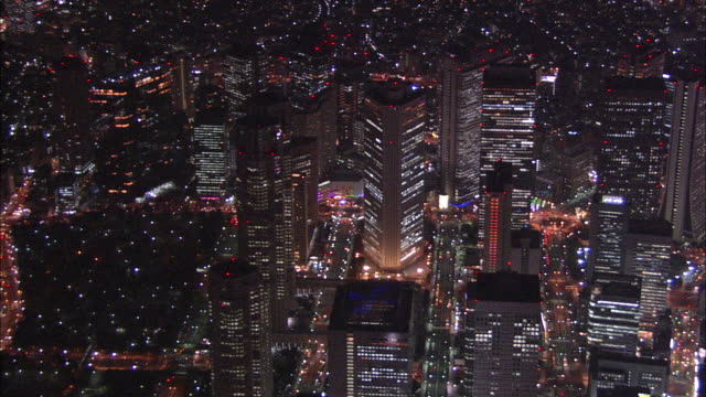 lights illuminate the shinjuku subcenter of tokyo at night. - heranzoomen stock-videos und b-roll-filmmaterial