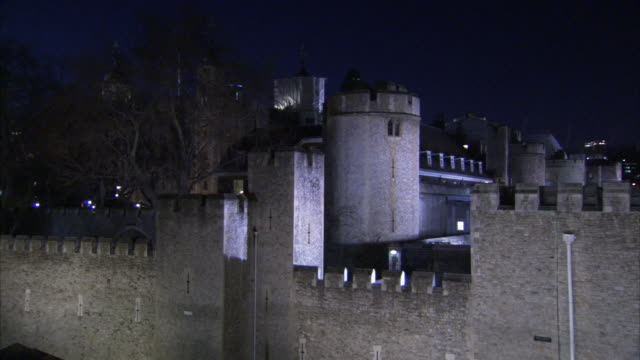 lights illuminate the tower of london and its surrounding walls at night. - castle stock videos & royalty-free footage