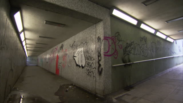 lights illuminates a dank pedestrian underpass covered in graffiti. - graffiti stock videos & royalty-free footage