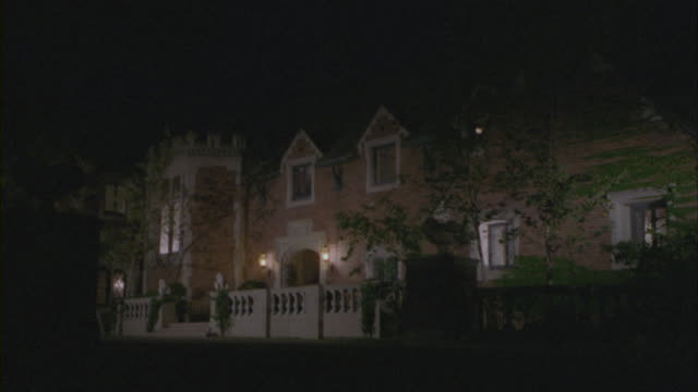 stockvideo's en b-roll-footage met lights illuminating the exterior of a tudor style mansion. - landhuis