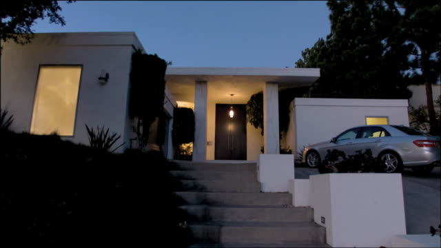 MS Lights illuminating the windows of a white, square home with car parked in driveway