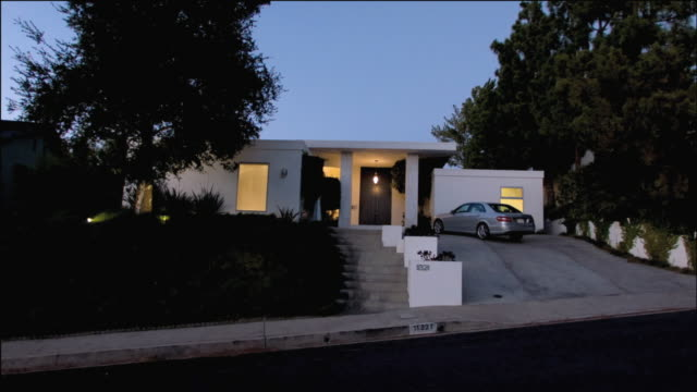 WS Lights illuminating the windows of a white, square home with car parked in driveway