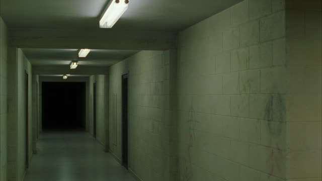ws lights of empty corridor turning off in sequence - korridor stock-videos und b-roll-filmmaterial