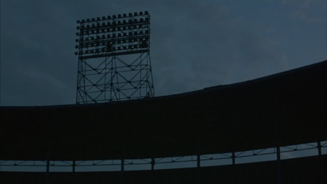 lights on a tower illuminate over an empty sports stadium. - floodlight stock videos & royalty-free footage