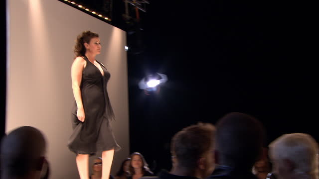 LA MS lights on ceiling/ TU MS PAN model in black dress walking onto catwalk/ LA MS Model posing at end of catwalk, turning, and walking back/ London, England