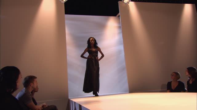 la ws lights on ceiling/ td ms pan model walking on catwalk at fashion show/ ms woman posing on catwalk, turning, and walking away/ london, england - この撮影のクリップをもっと見る 1064点の映像素材/bロール