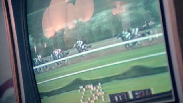 vídeos de stock e filmes b-roll de lights reflect in a television screen showing a horse race and the winning horse crossing the finish line. - jogos de azar