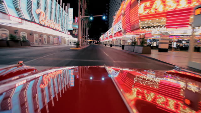 lights reflect off a car as it travels along the strip in las vegas. - kasino stock-videos und b-roll-filmmaterial