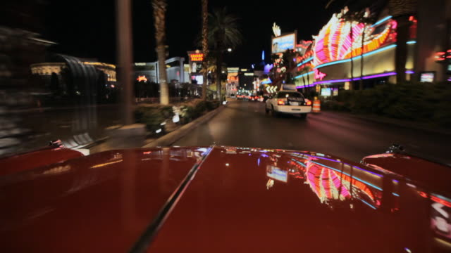 lights reflect off a car as it travels along the strip in las vegas. - ドライブ旅行点の映像素材/bロール