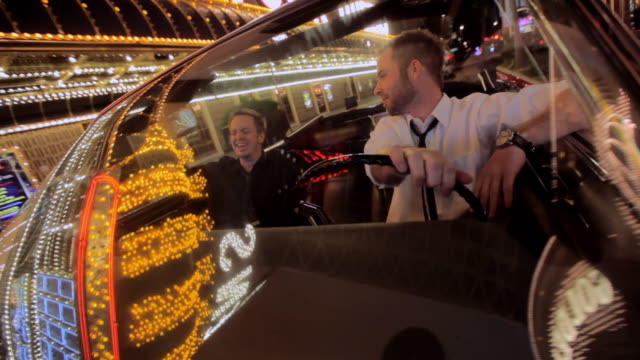 lights reflect off a convertible as a man drives it along the strip in las vegas. - man convertible stock videos & royalty-free footage