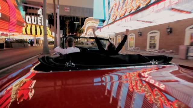 Lights reflect off a convertible as a man drives it along The Strip in Las Vegas.