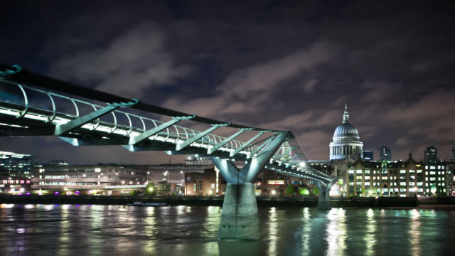 Lights reflect on the Thames River under the Millennium Bridge in London, England.