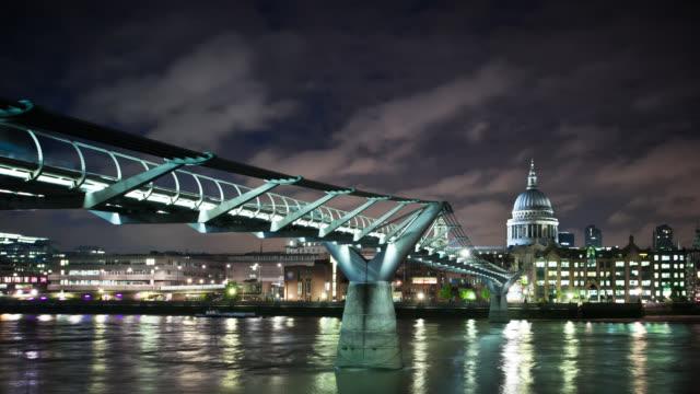 lights reflect on the thames river under the millennium bridge in london, england. - london millennium footbridge stock videos and b-roll footage