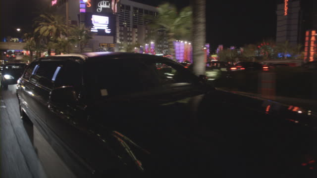 lights reflecting off a shiny limo as it cruises down a street in las vegas at night. - limousine stock videos & royalty-free footage