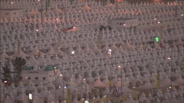 lights seem to sparkle above the white tents of the hajj terminal tent city in saudi arabia. - hajj stock-videos und b-roll-filmmaterial