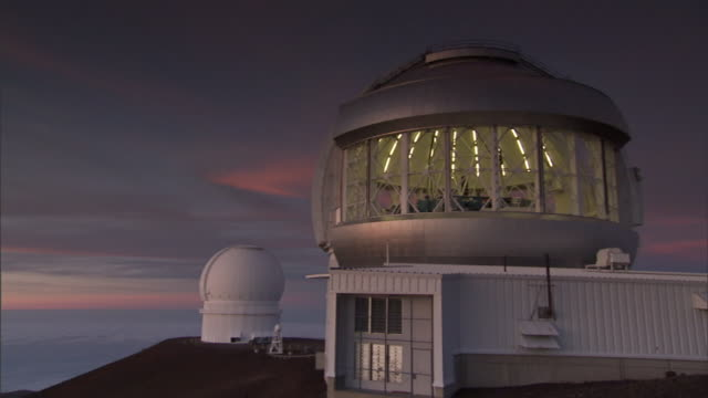 lights shine behind the exterior windows of a domed building at w. m. keck observatory on hawaii's big island. - observatory stock videos & royalty-free footage
