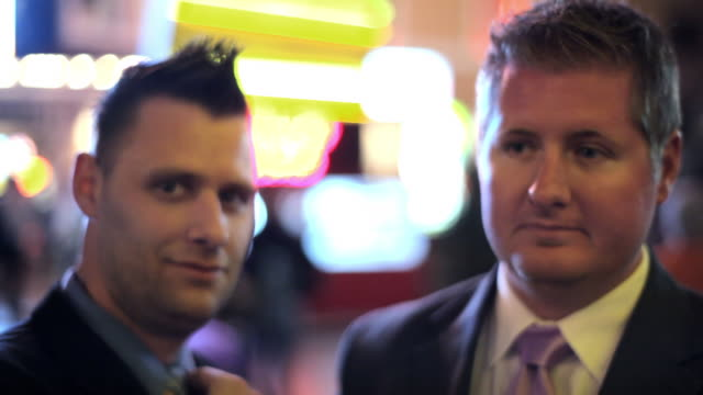 lights shine behind two businessmen on the strip in las vegas. - 全套西裝 個影片檔及 b 捲影像