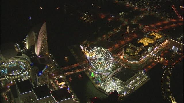 lights shine from the minato mirai ferris wheel in yokohama, japan. - yokohama stock videos and b-roll footage