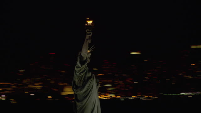 vídeos de stock, filmes e b-roll de lights shine from the new york skyline around the statue of liberty. - figura feminina