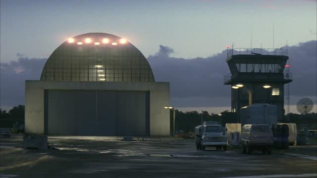 lights shine inside an airplane hangar. - hangar stock-videos und b-roll-filmmaterial