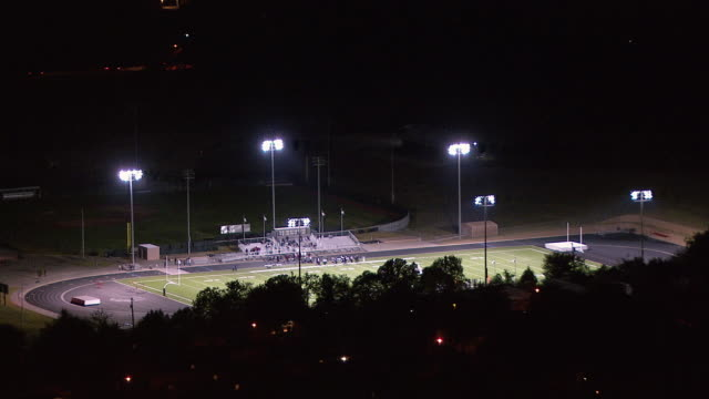 lights shine on a high school football field. - football pitch stock videos and b-roll footage