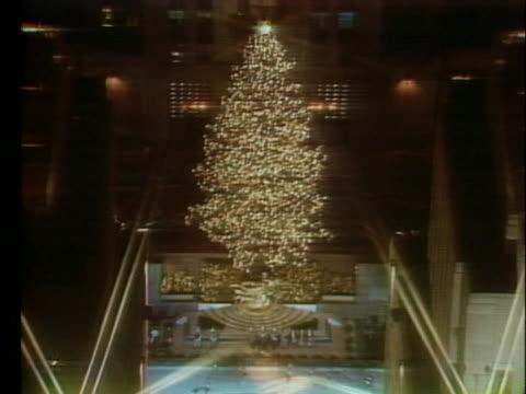 lights shine on the rockefeller center christmas tree in new york city. - albero di natale del rockefeller center video stock e b–roll